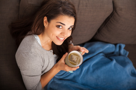 top angle: Top view of a happy young Latin woman covered in a quilt and drinking tea Stock Photo