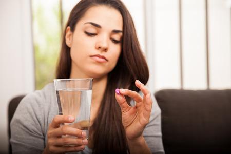 pastillas: Bastante joven mujer con una p�ldora del d�a despu�s y un vaso de agua en el hogar Foto de archivo