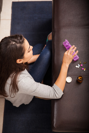 Top view of a young woman sorting and organizing some of her vitamins at home photo