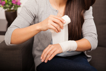 Closeup of a young woman removing a bandage from her arm at home