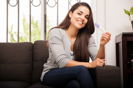 Excited Hispanic young woman holding a pregnancy test and smiling photo