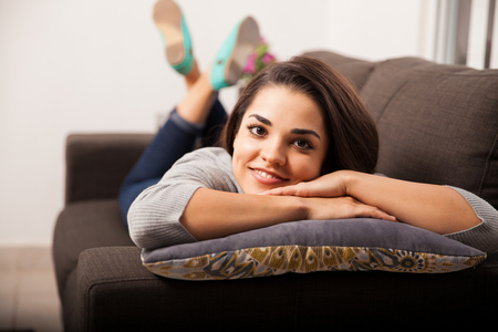 Portrait of a beautiful young Latin woman laying on a couch at home and smiling photo