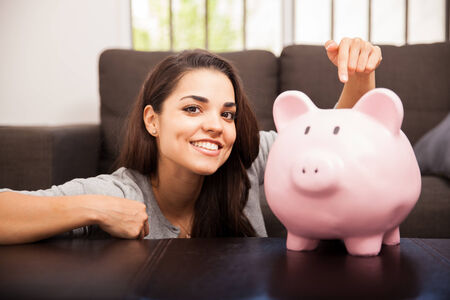 money savings: Gorgeous brunette pointing at a piggy bank in the living room and smiling