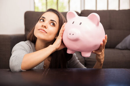 Beautiful young woman shaking a piggy bank and listening to its contents photo