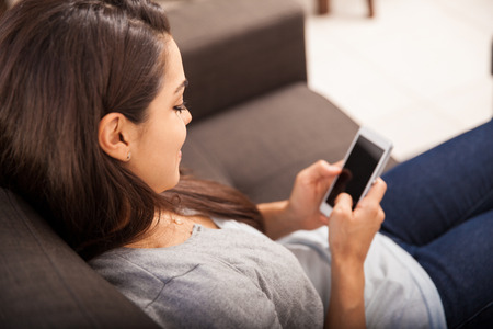 woman on couch: Point of view of a young woman using a smart phone for texting. Focus on the woman Stock Photo
