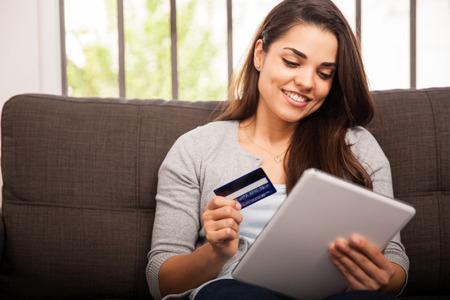 chicas de compras: Mujer joven linda compras en l�nea con su tarjeta de cr�dito y una computadora tableta en casa