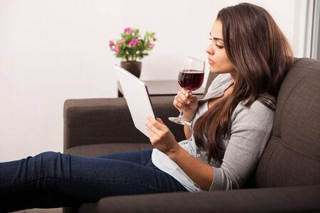 sorbo: Bastante joven morena de tomar un sorbo de vino mientras se utiliza un ordenador tableta en casa Foto de archivo