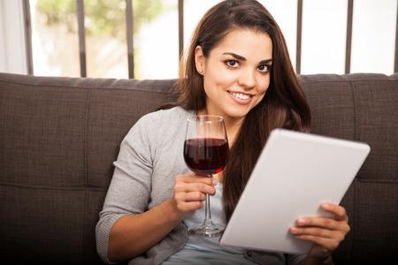 Cute Latin girl having a glass of wine at home and reading on a tablet computer photo