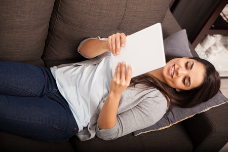 Top view of a cute young woman laying on a couch and reading on tablet computer photo