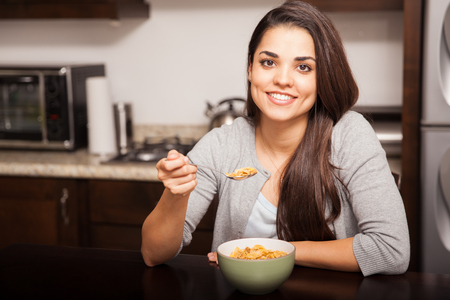 Happy young Latin woman enjoying a bowl of cereal for breakfast at home