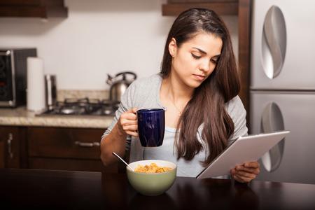cereales: Mujer joven con un tablet PC para leer las noticias y algunos mensajes de correo electr�nico mientras toma el desayuno en casa