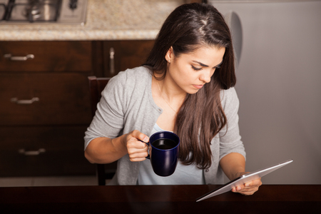 news room: Cute brunette reading the news on her tablet computer while enjoying a cup of coffee
