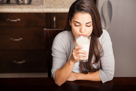 sip: Top view of a beautiful young woman taking a sip of milk for breakfast in the kitchen Stock Photo