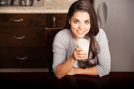 woman drinking milk: Pretty young brunette enjoying a glass of milk at home and smiling