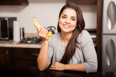 banana: Gorgeous young woman about to eat a banana at home and smiling Stock Photo