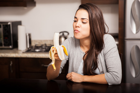 건강한 젊은 여성이 부엌에 앉아있는 동안 바나나를 먹고 스톡 콘텐츠