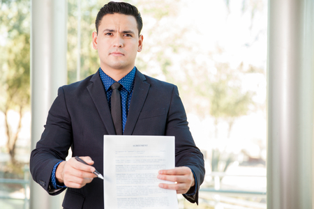 requesting: Portrait of a young Hispanic lawyer holding a contract and a pen and requesting a signature Stock Photo
