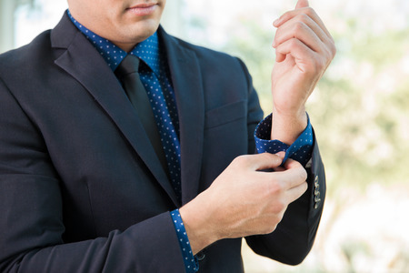 the sleeve: Closeup of a young businessman fixing up his sleeve and looking sharp for a job interview Stock Photo
