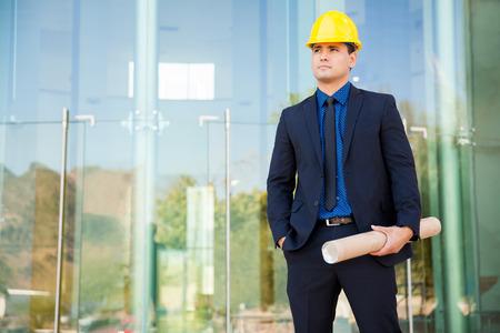ingeniero civil: Atractivo ingeniero civil joven que llevaba un casco y un traje y supervisar un proyecto de construcción Foto de archivo
