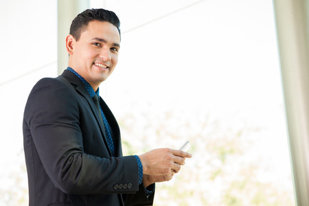 Happy young Latin businessman using a smart phone at work Stock Photo