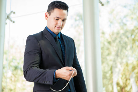looking at watch: Attractive young businessman looking at the time on his pocket watch Stock Photo