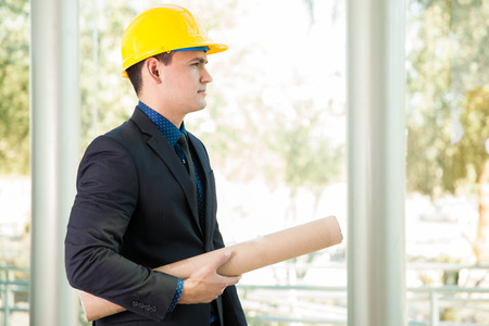 Profile view of a young business investor wearing a helmet while visiting a building site photo