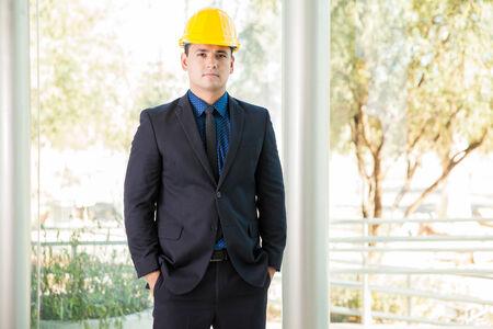 ingeniero civil: Retrato de un joven ingeniero civil con un traje y un casco
