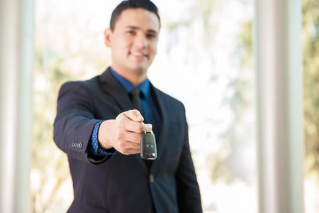 sales rep: Attractive Hispanic salesman handing over the keys of a new car. Focus on keys