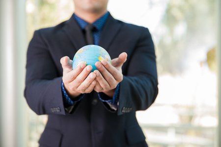hands holding globe: Closeup of a man wearing a suit and holding a small globe in his hands