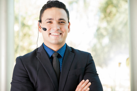 Good-looking customer service representative wearing a suit and a headset and speaking with a smile