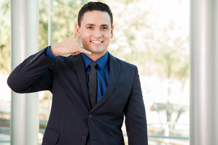 Attractive Latin businessman inviting customers to call and do business Stock fotó