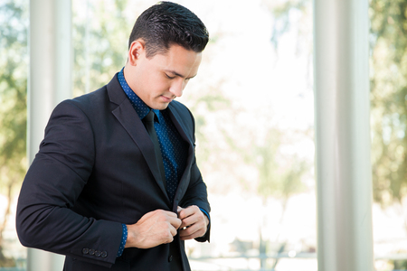 getting ready: Young handsome man in a suit buttoning his jacket and getting ready for a meeting at work Stock Photo
