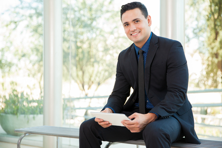 happy business man: Portrait of a young Hispanic businessman using a tablet computer for work and smiling Stock Photo