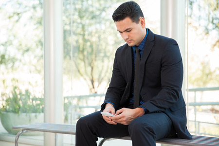 adult texting: Young businessman texting and social networking with his smart phone at work