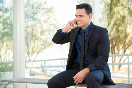 latin man: Handsome young lawyer talking over the phone with some clients Stock Photo