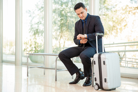 looking at watch: Handsome young businessman looking at his watch while waiting for a flight at an airport Stock Photo
