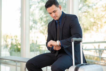 looking at watch: Young Latin businessman looking at his watch while waiting for his flight at an airport