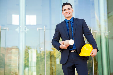 Young Hispanic investor in a suit visiting a construction site and carrying a helmet and blueprints