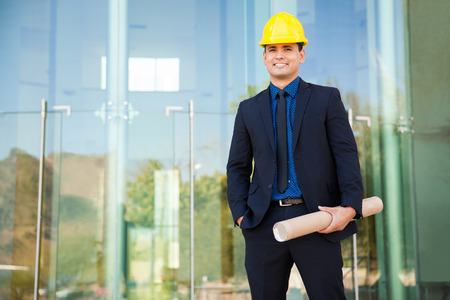 civil engineer: Handsome young Hispanic architect wearing a suit and helmet and visiting one of his projects