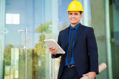 worker civil engineer: Retrato de un joven ingeniero guapo con un traje y un casco con un tablet PC en una obra en construcción Foto de archivo