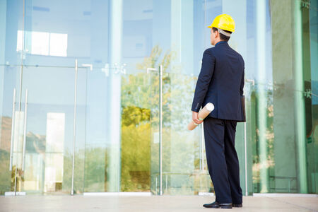 architect: Rear view of an architect wearing a suit and a helmet and looking at his almost finished building Stock Photo