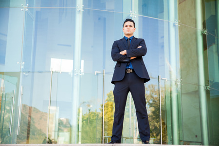 Young and powerful Hispanic lawyer and politician standing in front of a building, arms crossed photo