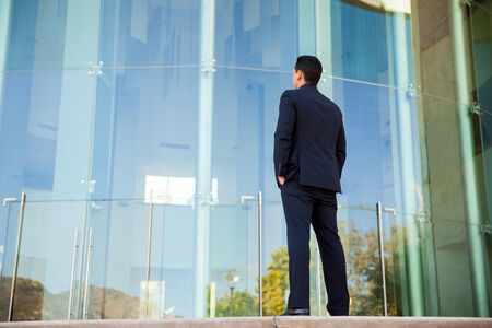 Rear view of a young business student in a suit looking at a school building