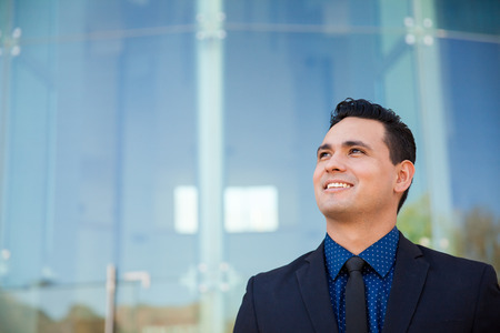 aspiring: Young aspiring man in a business suit looking up towards copy space and smiling