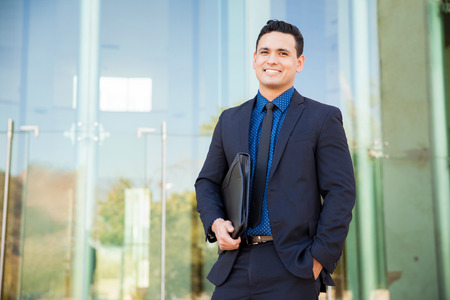 Handsome Hispanic man in a suit carrying his resume and waiting for a job interview and smiling Banco de Imagens