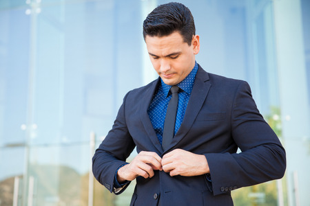 buttoning: Attractive young businessman buttoning his jacket and fixing his suit before going into an important meeting Stock Photo