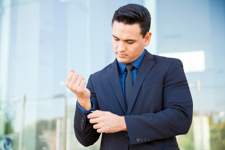 sleeve: Hispanic man in a suit buttoning his sleeve and fixing up his suit before a business presentation