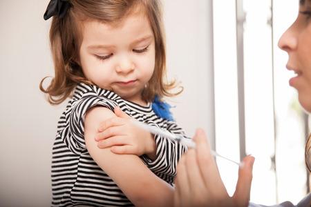 gripe: Primer plano de una linda niña vacunarse contra la gripe a un médico