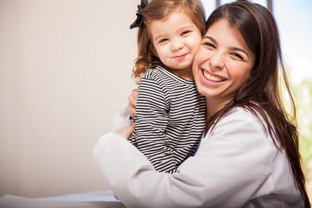 小さな女の子と彼女に抱擁を与える彼女の患者の 1 つとして幸せなヒスパニック系の小児科医の肖像画