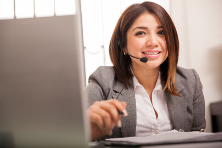 customer service representative: Beautiful young woman in a suit wearing a headset and taking calls from customers Stock Photo